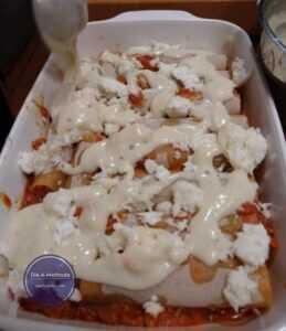 Béchamelsauce auf Cannelloni verteilen